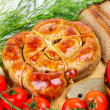 Stock Photo: Ring bratwurst with bread, tomatoes and herbs.