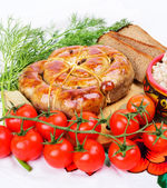 Ring bratwurst with bread, tomatoes and herbs. — Zdjęcie stockowe