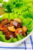 Marinated mushrooms with lettuce leaves. — Stock Photo