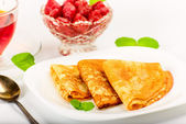 Russian pancakes with black tea and strawberries. — Stock Photo