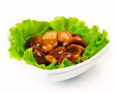 Marinated mushrooms with lettuce leaves. — Stock Photo