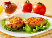 Two chicken cutlets on the green leaf lettuce. — Stock Photo