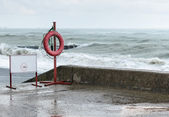 Warning sign and a life buoy — Foto Stock