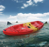 Boat with sharks around — Stock Photo