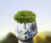 Holding a glowing earth (NASA) globe and tree in his hand — Stock Photo