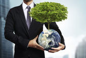 Holding a glowing earth (NASA) globe and tree in his hand — Stockfoto