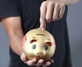 Hand putting coin into piggy bank — Stock Photo
