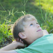 Stock Photo: Boy relaxing on green grass lawn
