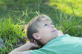 Boy relaxing on green grass lawn — Stock Photo