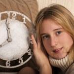 Smiling girl showing clock — Stock Photo
