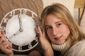 Smiling girl showing clock — Stok fotoğraf
