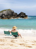 Elderly woman sitting at the beach — Stockfoto