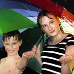 Happy kids walking under the rain — Stock Photo