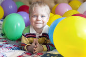 Smiling baby boy with balloons. — Stock Photo