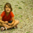 Stock Photo: Girl sitting on road. child sits cross legged on the