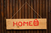 A wooden board hanging, with home written on it — Stock Photo