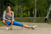 Woman warms her leg muscles before jogging — Stockfoto