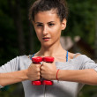 Attractive woman holding two weights together — Stock Photo