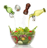 Pouring condiments on a colorful salad. isolated — Stock Photo