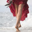 Sexy woman in red dress, steps on wet rock, next to sea — Stock Photo