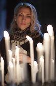 Piękną kobieta modli się, stoi za świece — Zdjęcie stockowe