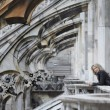 Blonde woman waits on ghotic cathedral balcony - Stock Photo
