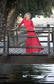 Beutiful woman in red dress, wooden bridge — Stock Photo