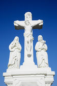 White crucifix sculpture and blue sky background — Stock Photo