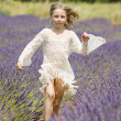Happy little girl jumps in field of lavender — Stock Photo