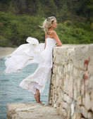 Young, beautiful and sexy woman, white dress, strong wind blows — Stock Photo