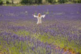 Beautiful little girl runs and jumps in the middle of a field of lavender — Stock Photo