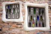 Colorful bottles embedded into brick wall — Stock Photo