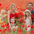 Happy family in poppy field — Stock Photo