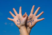 Linked hands with smiles and sadness pattern — Stock Photo