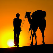Silhouette of a man and camel at sunset — Stock Photo