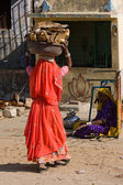 PUSHKAR, INDIA - NOVEMBER 18: An unidentified woman with firewood on their head attends the Pushkar Camel Mela on November 18, 2012 in Pushkar, Rajasthan, India. This fair is the largest camel trading — Stock Photo