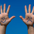 Hands with smiles and sadness pattern against the blue sky — Stock Photo #22438003
