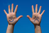 Hands with smiles and sadness pattern against the blue sky — Stock Photo