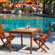 Table and chairs next to the pool, Thailand — Stock Photo #22668739