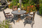 Table and chairs in a tropical garden, Thailand — Stock Photo