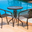 Stock Photo: Table and chairs next to the pool