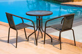 Table and chairs next to the pool — Stock Photo