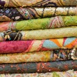 Foto Stock: Heap of cloth fabrics at local market in India. Close up .