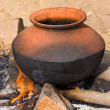 Clay pot with food on fire, India — Stock Photo #26732463