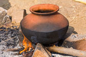 Clay pot with food on fire, India — Stock Photo