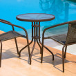 Table with chairs standing against the swimming pool — Stock Photo