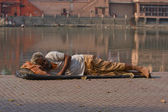 HARIDWAR, INDIA - NOV 8: An unidentified homeless man sleeps on the sidewalk near the River Ganges on November 8, 2012 in Haridwar, India. Poor Indians flock to Haridwar for charity. — Stock Photo