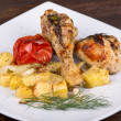 Foto Stock: Grilled chicken legs with potato and vegetables