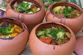 Meat baked with vegetables in rustic clay pot — Stock Photo