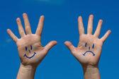 Mãos com sorrisos e padrão de tristeza — Foto Stock